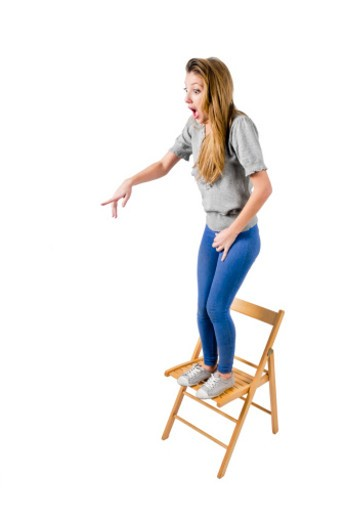 Frightened Young teen girl stands on a chair pointing at the threat (not depicted) : Stock Photo