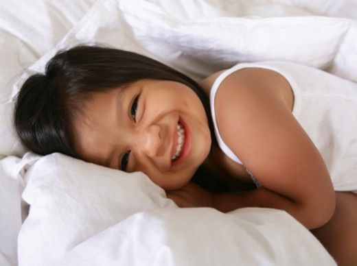 Young girl in bed smiling at camera : Stock Photo
