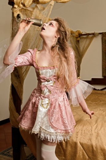 Stock Photo: 1672R-63616 Girl in a bedroom drinking from a chalice