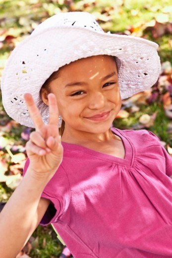 Girl giving peace sign : Stock Photo