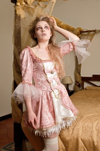 Girl in costume beside a bed : Stock Photo