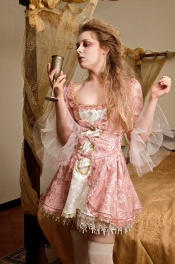 Stock Photo: 1672R-64640 Girl in a bedroom drinking from a chalice