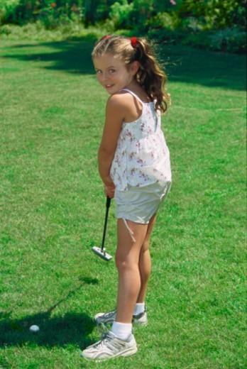 Girl (7-9) putting golf ball on lawn, portrait : Stock Photo