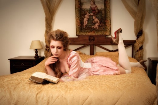 Girl reading on bed : Stock Photo
