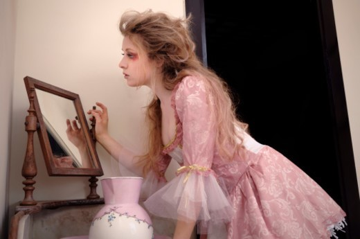 Stock Photo: 1672R-65480 Girl looks in the mirror dressed