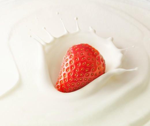 Strawberry splashing into cream : Stock Photo