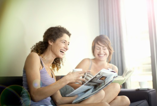 Two young women reading magazines share a joke : Stock Photo