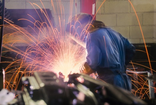 Welder working in car factory : Stock Photo