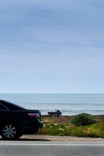 Couple enjoying the Pacific ocean, Highway 1 in the foreground. : Stock Photo