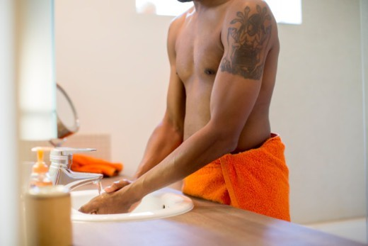 Close-up of a man in towel washing his hands : Stock Photo