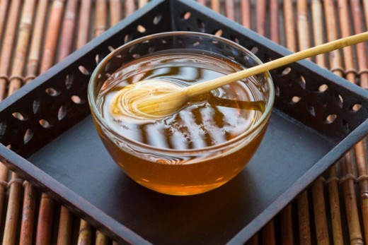 Stock Photo: 1672R-67653 A bowl of honey on a  wooden tray