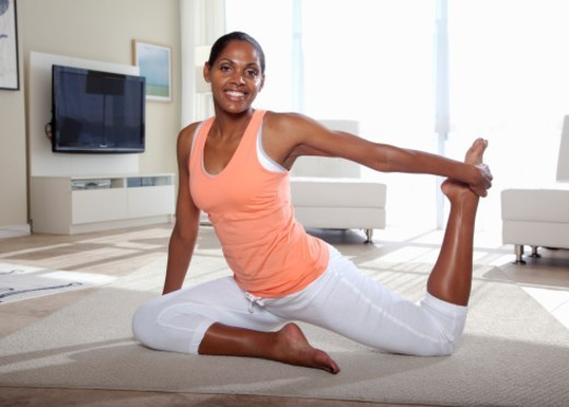 African American woman exercising at home : Stock Photo
