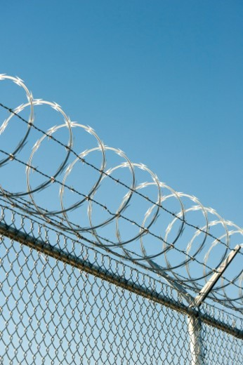 Razor and barbed wire topping a security fence : Stock Photo