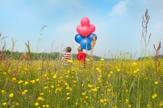 Stock Photo: 1672R-69436 Children holding balloons in a meadow of flowers