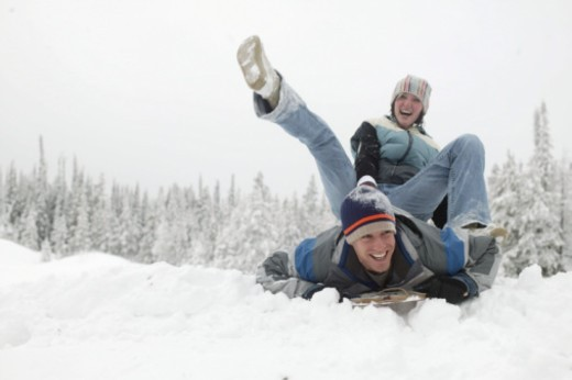 Young man and woman on sled on snowy hillside, low angle view : Stock Photo