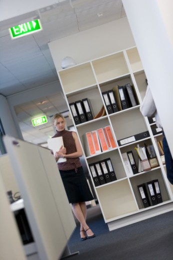 Woman leaning against bookcase in office, looking towards colleague : Stock Photo
