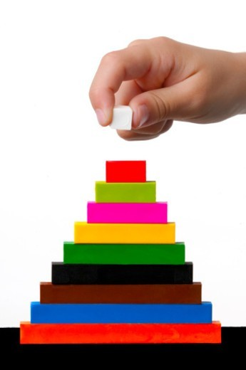 Child's hand stacking blocks : Stock Photo