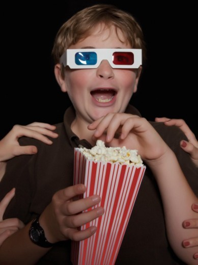 Hands grab a boy watching a 3-D movie with popcorn : Stock Photo