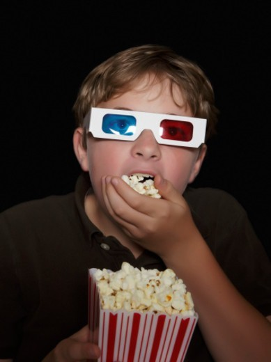 Boy watching a 3-D movie eating popcorn : Stock Photo