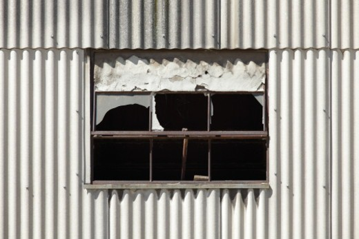 Broken window in a wall of corrugated steel : Stock Photo