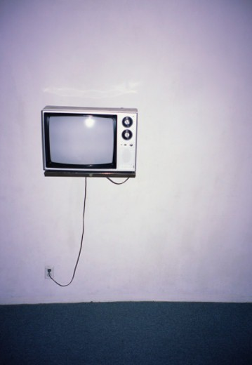 Obsolete TV hanging on a motel wall. : Stock Photo