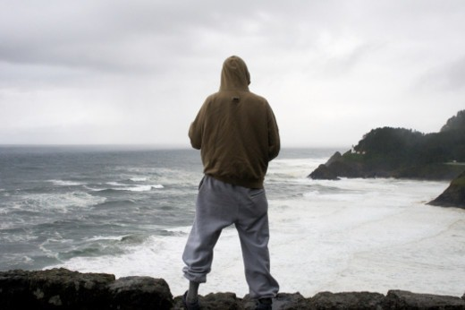 Stock Photo: 1672R-74156 Man in sweat suit looking out over the Pacific Ocean with the Haceta Head lighthouse.