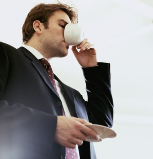 Businessman drinking from cup and saucer, low angle view : Stock Photo
