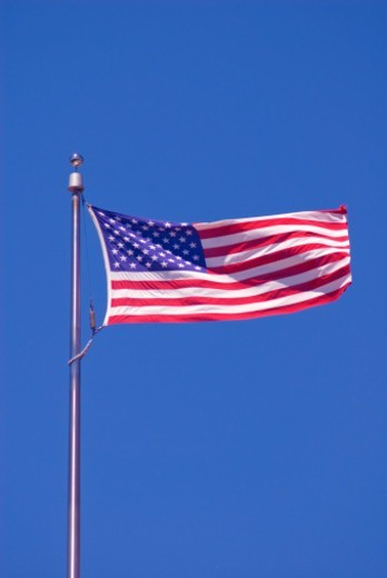 Stock Photo: 1672R-74295 American flag flying against a blue sky