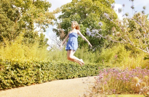 Stock Photo: 1672R-74717 Young woman floating through a wild summer garden