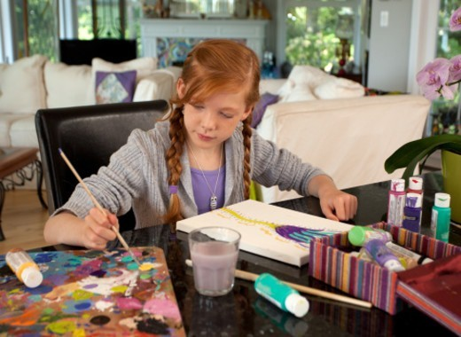 11 year old girl painting at home : Stock Photo