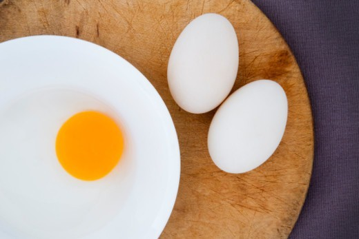 Two ducks on a board and a broken egg in a bowl : Stock Photo