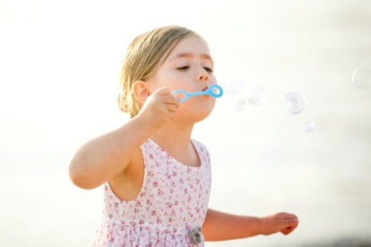 Stock Photo: 1672R-75280 Young girl holding a bubble wand and concentrating hard on blowing soap bubbles
