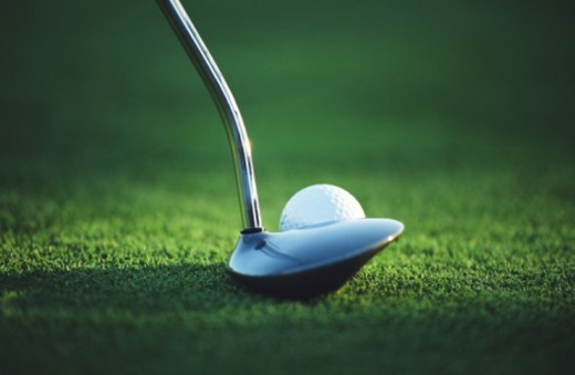 Stock Photo: 1672R-7569 Putter by golf ball on green
