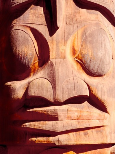 The carved symbols on totem poles recount legends, stories, cultural beliefs, shamanic powers and notable events. : Stock Photo