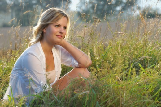 Stock Photo: 1672R-76780 Portrait of young woman daydreaming in a field