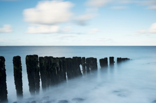 Stock Photo: 1672R-78691 Decaying wooden groin on a beach at high tide, long exposure, blurred motion.