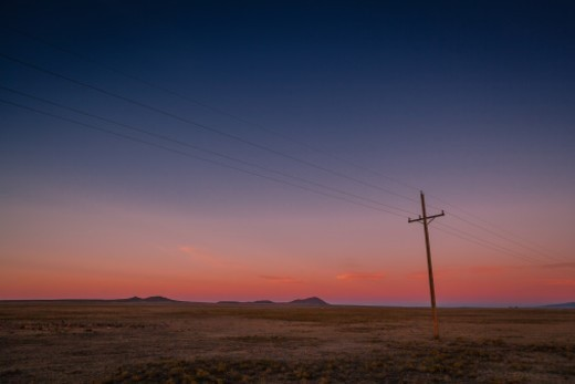 A quiet and beautiful sunrise with an old set of leaning powerlines in the high plains. : Stock Photo