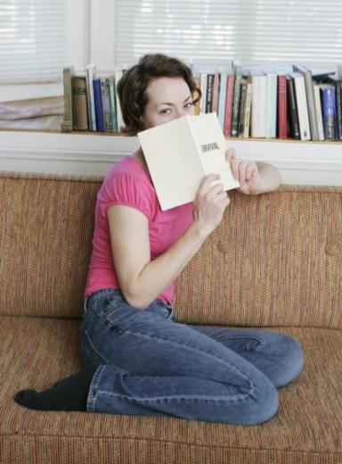 Woman sitting on sofa, peeking over book, portrait : Stock Photo