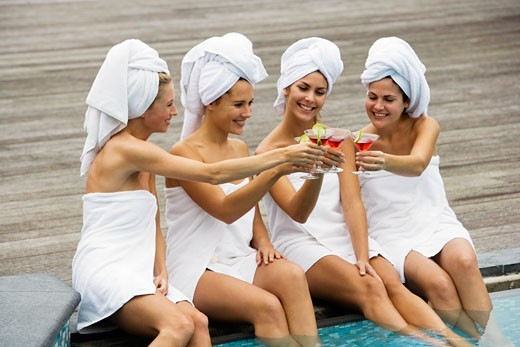 Stock Photo: 1676-105 Four young women toasting at poolside