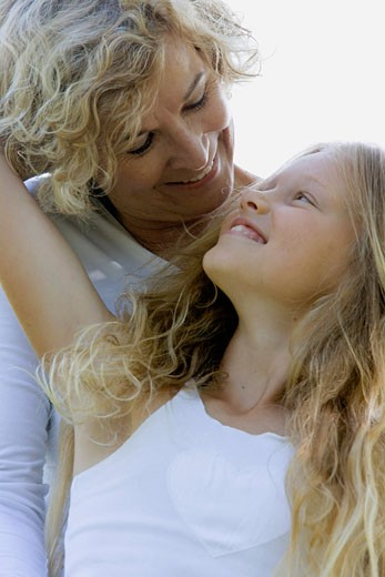 Close-up of a senior woman and her granddaughter looking at each other : Stock Photo