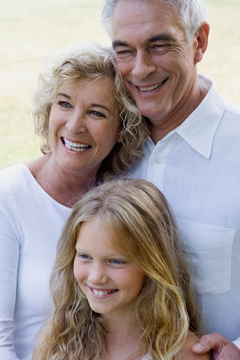 Close-up of a senior couple and their granddaughter smiling : Stock Photo
