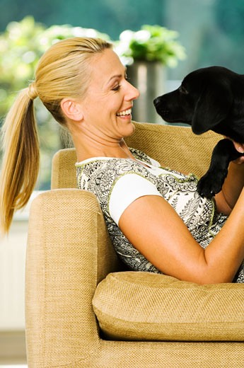 Stock Photo: 1679-116 Side profile of a mid adult woman lying on a couch playing with her dog