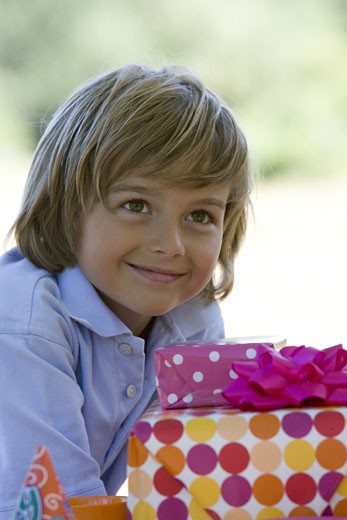 Close-up of a boy sitting near birthday presents : Stock Photo