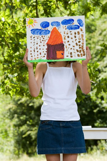 Close-up of a girl holding a painting in front of her face : Stock Photo