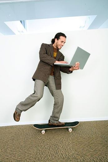Businessman riding a skateboard and using a laptop : Stock Photo