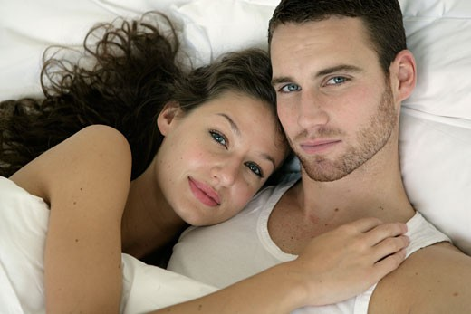 Portrait of a young couple lying in bed : Stock Photo