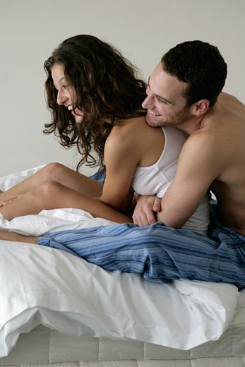 Young man embracing a young woman from behind in bed : Stock Photo