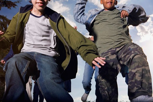 Low angle view of two boys jumping : Stock Photo