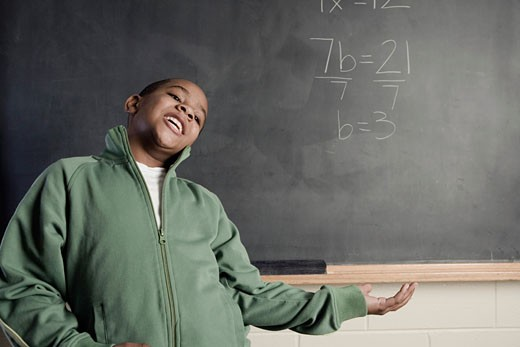 Boy in front of a chalkboard near a math problem : Stock Photo