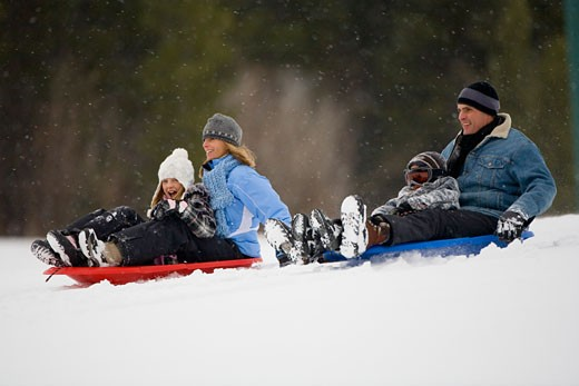 Stock Photo: 1698-136 Mature couple sledding with their son and daughter